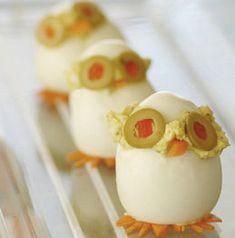 comida para niños, huevos rellenos: Un huevo cocido, corta a la altura de los ojos y pon el relleno con una altura de un dedo, eso servirá para adherir las lonchas de aceituna como ojos y el trocito de zanahoria como nariz. Pon la tapa que has cortado para cerrar el muñeco y hazle los pies recortando rodajas de zanahoria. Voilà! En la web hay un vídeo.