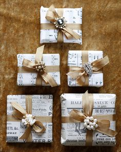 inspiration photo. Small packages wrapped in old sheet music, or newsprint, then tied up with a gold ribbon and a vintage piece of jewelry finishes it off.