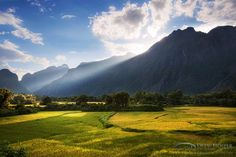 Sun breaks through the clouds and illuminates the rice fields below the mountains in Vang Vieng, Laos