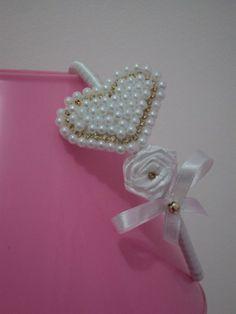 Tiara flexível forrada em cetim branco, coração bordado em pérolas brancas e strass dourado, flor de cetim branco e laço branco e dourado