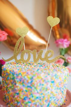 "Gold glitter ""love"" cursive cake topper on top of a sprinkle-covered one-tier wedding cake! Design by @bashandcoparty {Scarlet O'Neill}"