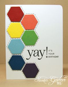 handmade birthday card by Susan Goetter ... clean and simple ... large pattern of die cut hexagons ... rainbow colors arranged in order and almost an arc ... like the faux stitching hand drawn around the perimeters ... luv how the sentiment is stamped on card base but starting inside the row of hexagons ... PTI birthday sentiment ... great card!!