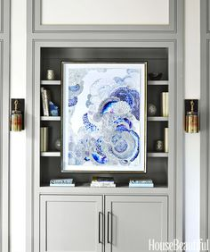 """A painting by Alexis MacIntire """"relates to the family room's ocean blues and the glittering silver of the metallic nailheads on the ottoman,"""" Kong says. Luna sconces, Ro Sham Beaux."""