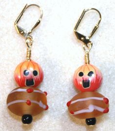 Handcrafted by Teal Palmetto, LLC.  These pumpkin creatures are sure to spook you!  Polymer clay pumpkin face beads sit atop frosted glass beads and black glass seed beads.  This pair has gold leverback ear wires.  Price: $11.