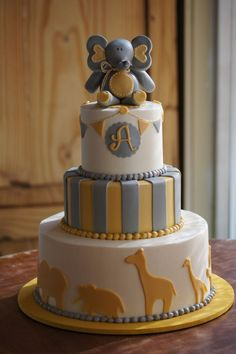 Yellow and grey animal themed baby shower cake with fondant elephant topper