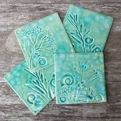 Set of 4 ceramic coasters with shells, seaweed and fossils from Charmouth near Lyme Regis, Dorset, pressed into soft clay, fired and glazed with spring green and turquoise blushed with pink and sea green crackle glaze. READY TO SHIP I collected all these sea things from nearby beaches at Charmouth, Seatown and Lyme Regis on the Jurassic coast, Dorset. It is so beautiful and full of stunning fossils. Here I have used iron pyrites ammonites, and others fossils which have turned to stone…