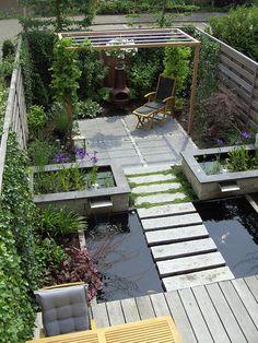 Koi-vijver met natuurlijk plantenfilter en zwevende stapstenen van natuursteen. Aangelegd en ontworpen door Garden Vision.