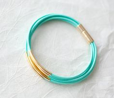 leather bracelet with small golden tubes