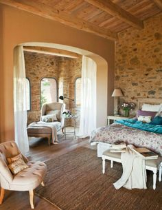 Exposed brick/stone w a sideways bed... neutrals and a chaise