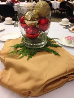 President's Club 2015- This tablescape is made up of Christmas ornaments in a vase, atop a glass block covered in gold and red fabric.