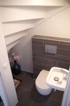 Showing how a cloakroom can be tucked away under the hall stairs. Genius idea.