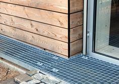Der gleiche Blick von außen: Vor der Holzfassade befindet sich ein Gitterrost. Darunter liegt eine Rinne für das Regenwasser. Das Gitterrost verhindert vom Boden gegen die Fassade spritzendes Wasser, das auf Dauer Spuren auf dem Holz hinterlassen würde.