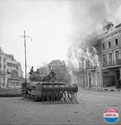 Arnhem: (Courtesy Imperial War Museum London) Een Britse Sherman Crab flail tank op de Utrechtsestraat tegenover het station. Crab flail tanks werden gebruikt om mijnen onschadelijk te maken. De kettingen sloegen al draaiend tegen de grond, en wanneer een landmijn werd geraakt ontplofte deze. Simpel maar uiterst doeltreffend. De gebouwen staan in brand en raakten daardoor dermate beschadigd dat ze na de oorlog moesten worden afgebroken. In de verte staat nog wel het oude Hotel Haarhuis…