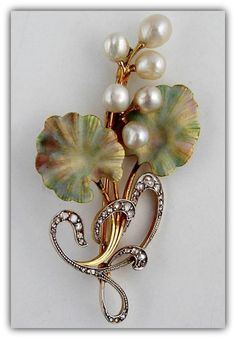 An Art Nouveau enamel, pearl and diamond brooch, the sinuous curling spray with six graduated pearl berries and opalescent shaded enamel leaves in pale pink, green and gold, to a yellow gold curved branch with rose diamond set scrolled ribbon tie, millegrain platinum set to a yellow gold mount, bearing indistinct marks to the reverse, measuring approximately 6cm, gross weight 9.6 grams, circa 1900.