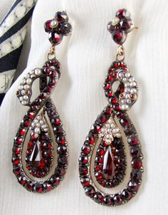 Victorian snake garnet earrings --  Sumptuous garnets and natural seed pearls accent a bold snake design.  The rose cut garnets have an intense claret color and are full of sparkle.    The snake motif has been in use since antiquity.   Eternal love and eternal life are just a few of the meanings attributed to the snake. Queen Victoria chose a snake ring to mark her engagement to Albert.   Consequently, the snake became a popular Victorian romantic image used quite frequently
