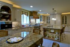 Gorgeous shaker-style cabinets stretch the length of this incredibly spacious eat-in kitchen by David Stimmel. Sunny yellow walls create a cheerful space for friends and family to gather. Seating at the island is available as well as the hightop table topped with the beautiful granite found throughout the kitchen.