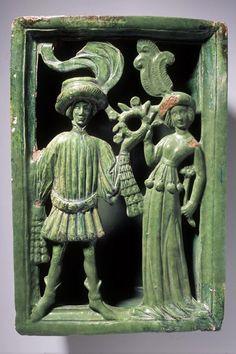 Füllkachel Nischenkachel mit Liebespaar mit Kranz, grün glasiert über weisser Engobe. Inhalt: Mann. Um 1430. Herkunft: Effretikon (ZH), Moosburg Bodengrabung. 30,5 x 21 cm (Breite rekonstruiert). Keramik, glasiert, engobiert.