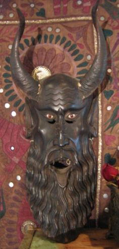 "This is the real thing, a one-of-a kind artifact! Hand-carved dark wood mask with real 10"" goat horns and marble eyes. Made by indians in the mountains of the mexican state of guerrero for the folk ""santos y diablos"" festival. Depicts a stylized horned devil with a long beard, piercing eyes, fangs and a hanging tongue, carved in intricate detail. Size: approx. 24""x9"". 3lbs."