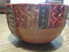 Bols de barro rojo, hecho en molde de yeso con guarda impresa, pintado con esmalte rojo y óxido de cobre.