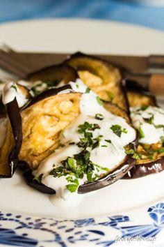 Aubergines Grillées, Yaourt aux Herbes. Ingrédients : 1 aubergine - Huile d'olive - Sel - Poivre noir - persil plat - menthe - 1yaourt brassé  Préchauffez le four à 180°. Coupez l'aubergine en tranches. Badigeonnez légèrement sur chaque face d'huile d'olive à l'aide d'un pinceau. Salez et poivrez. Enfournez 15 minutes. Préparez le yaourt en y ajoutant du persil plat et de la menthe ciselé finement. Salez et poivrez. Servez les aubergines tièdes avec du yaourt et parsemez d'herbes.