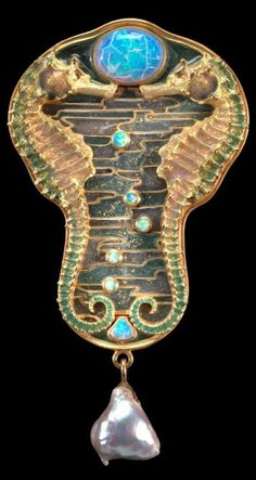 An Art Nouveau brooch, by René Lalique, 1902-05. Designed as two realistically carved seahorses decorated with enamel, against an enamelled background representing sea waves, highlighted with cabochon opals, suspending an oriental pearl, mounted in yellow gold. #Lalique #ArtNouveau #brooch