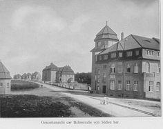 Schwarz-Weiß-Foto: Straße mit Häusern auf der rechten Seite