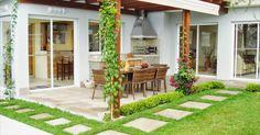 Área de lazer integrada à casa com cobertura em pergolado de madeira e vidro. Traz coifa em inox, revestimentos em pastilha cerâmica esmal...