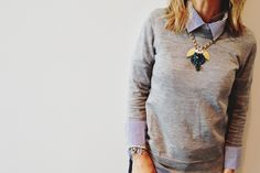love the striped shirt under a grey jumper and a big statement necklace