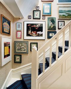 """From Domino Magazine. Love the idea of a """"busy"""" wall that follows stairs. I would use different sized photographic prints from my travels though, rather than a hodgepodge of art."""
