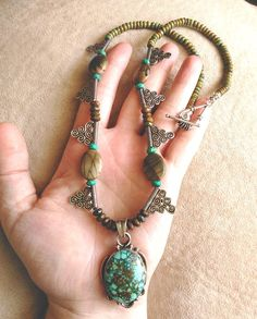 Gorgeous in green! This stunning southwestern-style statement necklace, was handmade using a lovely vintage Native American pendant (likely Navajo from the 1960's, based on the design elements present) of sea green and brown turquoise with a dramatic black spiderweb pattern, plus Red Creek jasper, oodles of brown and green turquoise rondelle beads, and sterling silver cloud / spiral accents. Enjoy :)
