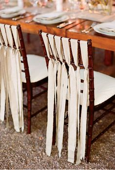 Chairs decorated with ribbon at wedding reception  The bride cut linen fabric into strips to embellish the reception chairs she and Jeff would use. Photo: Lisa Lefkowitz