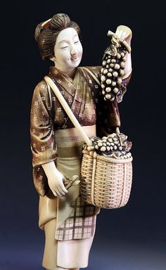 "Japan, 20th Century. Depicts A Farmer's Wife Harvesting Grapes. She Is Clothed In A Short Patterned Kimono And Apron, Her Left Hand Holding A Bunch Of Grapes Over A Full Basket Suspended To The Front, The Details Heightened With Brown And Black Pigment. 9""H."