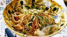 Stek lök och vitlök i olivolja utan att det det tar färg. Klipp tomaterna i bitar med en sax direkt ner i burken. Häll på vitt vin, vatten och tomater, låt koka i 10-15 minuter. Smaka av med salt, en nypa socker, peppar och basilika.   Koka pastan enligt anvisning på paketet. Blanda pastan med tomatsås och vänd ner mozzarellan. Strö över rucola. Servera med nyriven Grana Padano-ost.