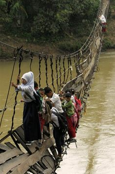 A troubled bridge over waters  Students cling to steel cables on a collapsed bridge as they cross a river to get to school, Jan. 19, at Sanghiang Tanjung village in Banten village, Indonesia. Flooding from the Ciberang River broke a pillar supporting the suspension bridge, built in 2001. Sofiah, a student crossing the bridge, says she would need to walk for an extra 30 minutes if she were to take a detour over another bridge.