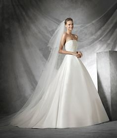 Simple, strapless princess wedding dress in mikado silk. Strapless bodice decorated with soutage and white gemstone embroidery.