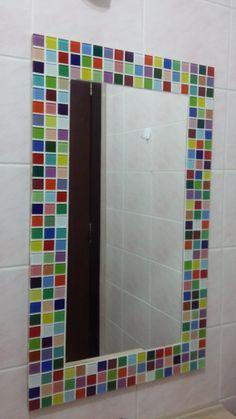 Espelho decorativo vertical com moldura em mosaico de pastilhas de vidro multicoloridas. <br>Um espelho que alegra o ambiente. <br> <br>Dimens�o da l�mina do espelho 30cm x 60 cm. <br>Dimens�o do espelho com moldura: 45 cm x 75 cm.