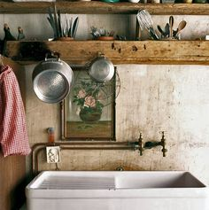 I love the old oak (walnut?) boards used as shelves in this very rustic kitchen.  Also heart the old butler's sink.
