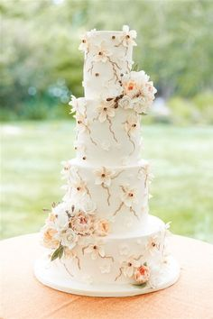 Gorgeous Fall wedding colors on this spectacular four tier wedding cake. Get wedding ideas and inspiration just like this on our website right now! #fallwedding #fallweddingdecorations #weddingcakeideas #weddingcaketable