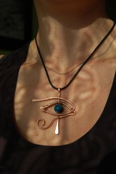 The Eye of Horus (Ra) is an ancient Egyptian symbol of protection, royal power and good health.  This pendant is made of copper wire with blue crackled glass bead as a pupil. The copper will age with time and cover with lovely patine. The purchase does not include the string, only the pendant.