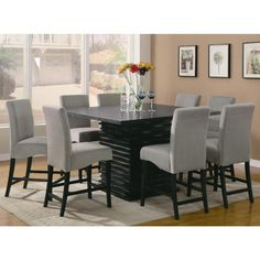Reinvent your dining room or bar area with this contemporary nine piece counter height table and chair set. The table in this set features a unique dazzling base.