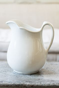 """Large antique ironstone pitcher in good condition. This pitcher has a simple body with a slightly scalloped rim. Pitcher has a few areas of discoloration and cracked glaze, but is in overall good condition. """"Carr China Co. Grafton, W. VA. 49"""", is stamped on bottom.Dimensions Base-Width: 4.75""""Length: 5.5""""Height: 10""""Length: (spout to handle) 9""""Handle height: 5.5"""" (US$65.00)"""