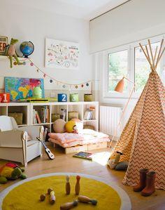 Habitación de juegos con tipi, alfombra redonda, estanterías bajas, butaca y palé a modo de sofá 00384420