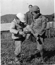 Two young boys play in front of a schoolhouse. The Japanese used education to erase Korean national identity in the latter part of their occupation; the Korean language was banned from schools and citizens were required to use Japanese names.