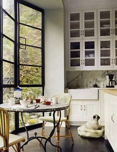 Katie Lee Joel's kitchen with green & cream bistro chairs, farmhouse sink, striped dog bed, and steel casement doors/windows (design by Nate Berkus, Domino)