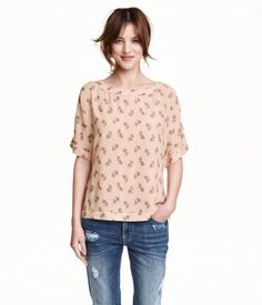 Short, wide-cut blouse in woven crêped fabric. Slightly wider neckline, short cap sleeves, and rounded hem with slits at sides.