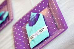 "Baby shower decorations - Place setting - Purple with white polka dot dinner plates topped with matching purple flatware. Flatware wrapped in aqua napkins and secured with ""Admit One"" tickets to incorporate the carnival theme."