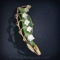From mid-twentieth century Austria comes this artful, multi-dimensional, hand carved nephrite leaf and frosted crystal lily of the valley brooch. The long graceful green leaf is supported by textured gold leaves and is enwrapped in golden stems. 2 5/8 inches long; signed Mandarbeit.