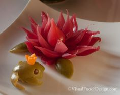 A VisualFood appetizer to garnish your plates. The water-lily is made out of pickled red onion. The frog prince is a green olive.