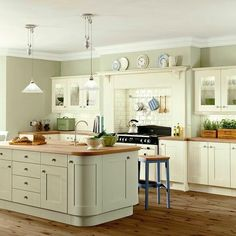 Re-painting my Mom's kitchen soon. I am thinking of going with a sage green  The kitchen has cream cabinets with a wooden counter top silver door hanflrs and a  cream tile backsplash. by homelylove