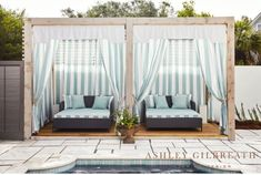 ASHLEY GILBREATH INTERIOR DESIGN: Blue and white cabana stripe pool cabanas with outdoor daybeds in performance fabric provide the perfect place for a day of relaxation by the pool! A limestone tile patio creates a sleek backdrop.